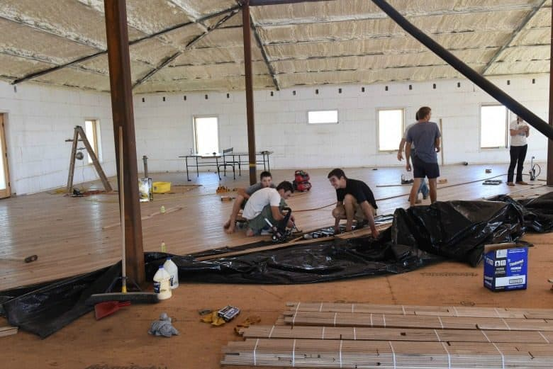 "Horizontal image from the post ""The Wood Floor Laying"" showing family laying oak flooring."