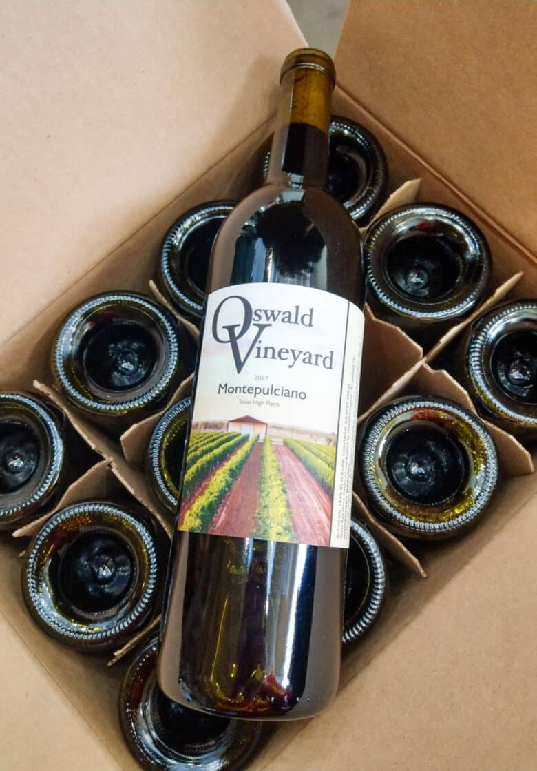 Labeling 2017 Vintage - a bottle of Montepulciano wine laying on top of an open case of wine.